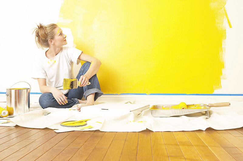 Pared pintada parcialmente de amarillo por una mujer joven sentada sobre un trozo de tela para proteger las posibles manchas de pintura